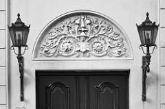 Stuckdekor / Relief über dem Eingang einer Villa in Hamburg Rotherbaum / Pöseldorf - eiserne Laternen, Lampen / Schwarz-Weiss.