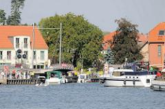 Sportboote warten vor der Drehbrücke in Malchow auf die Durchfahrt; das Signal steht jetzt auf Grün.