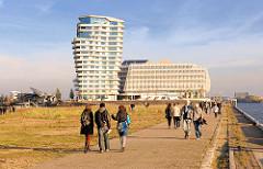 Spaziergang in der Abendsonne am Strandkai an der Norderelbe - lks. der Hübenerkai vom Grasbrookhafen - im Hintergrund das Unilever-Verwaltungsgebäude und der Wohnturm / Maco-Polo-Tower.
