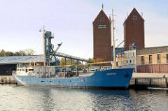 Speichergebäude / Silos im Kommunalhafen Neustadt / Ostholstein - Frachtschiff Pavona am Kai.