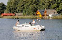 Angelboot und Bootshäuser am Mirower See - Hausdächer hinter Schilf am Seeufer.