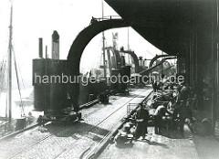 Altes Foto aus dem Hamburger Hafen - ein Brown'scher Dampfkran löscht am Strandhafen einen Frachter - Hafenarbeiter legen die Fracht in dem offenen Lagerschuppen auf Karren. (ca. 1905 )