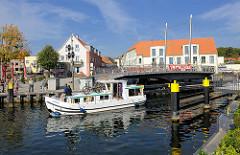 Geöffnete Drehbrücke in Malchow; ein Motorboot passiert die Durchfahrt.