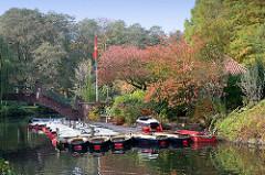 Bootsverleih auf der Liebesinsel im Hamburger Stadtparksee in Winterhude - Tretboote und Ruderboote liegen am Steg.