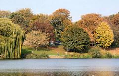 Blick über den Stadtparksee im Hamburger Stadtpark - Herbstbäume mit unterschiedlicher herbstlicher Blattfärbung am Ufer des Sees.