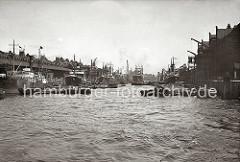 Blick in den Sandtorhafen; rechts der Kaiserkai - beladenen Schuten liegen am Kai, die Ladung ist mit Persenning abgedeckt. Im Hintergrund hinter dem Frachtschiff und Schwimmkran die Silhouette des Kaispeichers B. (ca. 1934)