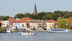 Wohnhäuser an der Hafenpromenade von Malchow am Malchower See - ein Ausflugsschiff legt ab; Kirchturm der Stadtkirche.