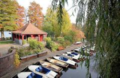Bootsverleih auf der Liebesinsel im Hamburger Stadtparksee in Winterhude - Tretboote und Ruderboote liegen am Steg - Sträucher und Bäume in herbstlichen Farben.