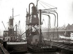 Ein schwimmender Getreideheber liegt im Sandtorhafen zwischen einem Lastkahn und einem Motorschiff; über vier Saugrüssel wird das Getreide vom Binnenschiff aufgenommen und in den Hamburger Dampfer ADOLPH KIRSTEN geladen. (ca. 1934)