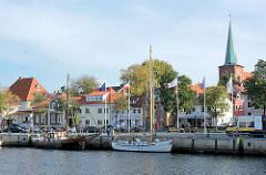 Blick über den Hafen von Neustadt in Holstein - Segelschiffe an der Hafenkante / Kai; Kirchturm der im 14. Jahrhundert erbauten Stadtkirche.