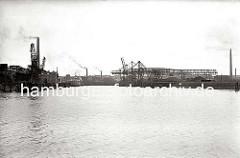 Blick von der Süderelbe in den Harburger Seehafen 2; am Kai befinden sich unter den Kränen Kohlehalden. Auf der linken Seite des Hafenbeckens liegen Schuten und ein Seeschiff an der Kaianlage. (ca. 1938)