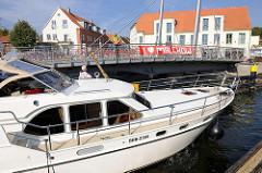 Geöffnete Drehbrücke in Malchow; ein Sportboot passiert die Durchfahrt.