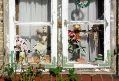 Altes Holzfenster mit Eisenwinkeln, abgeblätterte Farbe - Figuren als Fensterdekoration; Bilder aus Neustadt in Holstein.