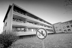 Dreistöckige Wohnanlage mit gelber Klinkerfassade, durchgehende Balkons mit Holzfassade - Schild Hunde verboten.