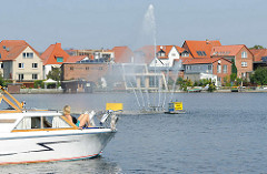 Wohnhäuser am Malchower See, Wasserspiel / Springbrunnen und Bug eines Sportboot / Motorboot.