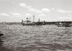 Der Frachter MARGARETA läuft geschleppt von dem Schlepper STOCKHOLM in den Hamburger Hafen ein - dahinter fährt ein Schleppverband auf dem breiten Hamburger Fluss.  Am Strandkai liegen Motorschiffe und Lastkähne. ( ca. 1936 )
