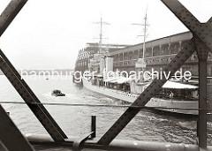 Blick durch die Eisenträger der Baakenbrücke auf den Magdeburger Hafen mit dem Fruchtschuppen C. Ein Marine Transportschiff hat am Kai fest gemacht. Ein Teil der Besatzung sitzt unter dem Sonnensegel am Heck des Schiffs. ( ca. 1934 )