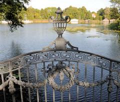 Gusseisernes Dekor, Zierelement an der Brücke der Mirower Schlossinsel - im Hintergrund Bootshäuser am Ufer des Mirower Sees.