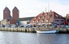 Zum Restaurant umgebautes altes Speichergebäude am Hafen von Neustadt in Holstein; Silotürme - Segelschiff am Kai.