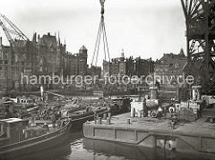 Im Sandtorhafen wird eine Lokomotive mit einem Schwimmkran aus dem Hafenbecken geborgen. Im Hintergrund die teilweise zerstörte Speicherstadt - an der Fassade des Verwaltungsgebäude der HHLA  ist ein Baugerüst zu erkennen. (1948)