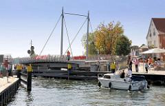 Ein Motorboot fährt durch die geöffnete Drehbrücke in Malchow / Malchower See - die Durchfahrtshöhe ist bei geschlossenem Zustand ca. 1,70m.