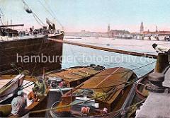 Ein Frachtschiff liegt mit einem Holzstamm abgebäumt am Kai des Hamburger Hafens. Der Baumstamm hält das Schiff auf Distanz zum Kai, so dass Schuten und Binnenschiffe dazwischen liegen können. ( ca. 1910 )