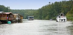 Bootshäuser am Müritz-Havel-Kanal - Sportboot und Hausboot in Fahrt; Wälder bis an das Ufer.
