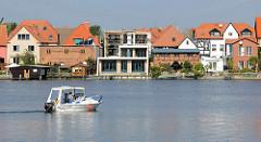 Wohnhäuser am Malchower See, Fachwerkgebäude und Neubau; Ziegelgebäude einer Aalräucherei, Fischhandlung.