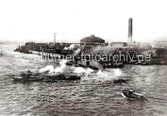 Ein Schleppverband kommt aus dem Magdeburger Hafen und überquert die Norderelbe - Binnenschiffe liegen bei den Schuppen des Magdeburger Hafens. Dahinter das Gelände der Gaswerke auf dem Grasbrook mit Gasometer. ( ca. 1911 )