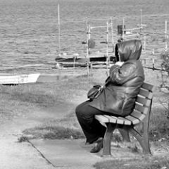 Ufer des Neustädter Binnenwassers - windiger, kühler Morgen, Frau mit dickem Mantel sitzt auf einer Bank am Wasser; Ruderboote, Fischerboote am Ufer des Sees.