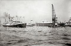 Das Motorschiff TANGER fährt auf der Elbe in den Hamburger Hafen ein, das Deck ist mit Fässern und Ballen hoch beladen. Am Strandhafen liegt ein Seeschiff im Strom an den Dückdalben. ( ca. 1938 )