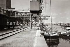 Mehrere große Elbkähne und motorisierte Binnenschiffe liegen an der Kaimauer eines der vier Harburger Seehafenbecken. Über eine Sauganlage wird die Ladung der Schiffe gelöscht und per Förderband in das Silo transportiert. (ca. 1938)