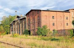 Gewerbegebäude, Industriearchitekur in Backsteinbauweise - Güterbahnhof Mirow; Eisenbahngleise mit Gras überwachsen.