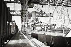 Im Harburger Seehafens wird die Kohleladung eines Dampfschiffs gelöscht. Die Greifer der Krananlage holen die Kohle aus dem Laderaum des Schiffs und verladen diese in die bereit stehenden stehenden offenen Güterwagen. (ca. 1938)