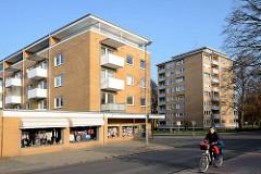 Mehrstöckige Wohnblocks mit gelber Ziegelfassade / Balkons - flache Ladengeschäfte; Harksheider Weg / Quickborn.