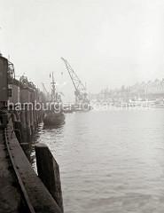 Einer der Schwimmkrane des Hamburger Hafens arbeitet am Kaiserkai / Sandtorhafen. Eine große Schiffsschraube hängt am Ausleger des Arbeitsschiffs. Auf dem Kai stehen die Rollkrane entlang der Schuppen auf den Gleisen. (ca. 1934)