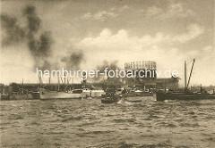 Blick über die Norderelbe zum Strandhafen im Hamburger Hafen - ein Schlepper zieht eine Kahn über die Elbe - Frachter liegen an Dalben im Strandhafen und am Strandkai; re. die Gasanstalt mit Gasometer am Magdeburger Hafen / Strandkai. ( ca. 1910 )