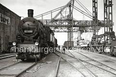 Eine Güterzugtenderlokomotive der Reihe 93 1008 rangiert auf den Gleisen am Harburger Seehafen - Güterwagen stehen am Kai neben einem Kohlenfrachter, dessen Ladung gerade gelöscht wird. (ca. 1938)