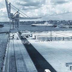 Containerkran am Hamburger Container Terminal Burchardkai - Blick über das Containerlager zur Elbe, ein Frachtschiff läuft aus dem Hamburger Hafen aus. ( ca. 1975 )