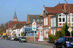 Unterschiedliche Architekturformen, Einzelhäuser mit Geschäften - Kieler Strasse in Quickborn; im Hintergrund der Kirchturm der Marienkirche.