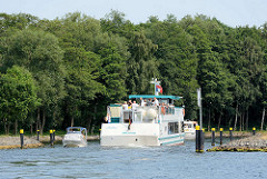 Schmale Einfahrt in den Fleesenkanal, Verbindung von Fleesensee und  Kölpinsee, Teil der Müritz Elde Wasserstrasse. Ein Auflugsschiff mit Touristen auf dem Oberdeck  fährt in den Kanal ein, ein Sportboot hat gerade Platz daran vorbei zu fahren.
