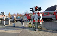 Fussgängerüberweg mit geschlossener Schranke und rotem Stopplicht am Bahnhof Quickborn - ein Zug der AKN fährt vorbei.