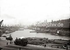 Die Schiffe liegen dicht an dicht an den Kaianlagen des Sandtorhafens. Im Vordergrund steht eine Lokomotive unter Dampf auf den Gleisen der Hafenbahn. Am Kai liegen Schuten, deren Ladungen sind teilweise mit Persenning abgedeckt. (ca. 1934)