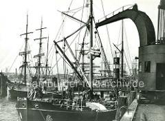Historisches Bild aus dem Hamburger Hafen; der Dampfer Achill löscht am Strandkai Kleie;  eine Hieve Säcke hängt am Rollkran - im Hintergrund Frachtsegler an den Dalben in der Elbe. (ca. 1905 )