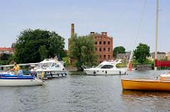 Auf Durchfahrt wartende Sportboote auf dem Malchower See, im Hintergrund die Ruine der alten Weberei / Spinnerei / Tuchfabrik  in Malchow; erbaut 1908, 1990 stillgelegt.