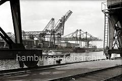 Blick über das Hafenbecken des Harburger Seehafens; im Vordergrund die Räder auf denen die Halbportalkräne auf der Kaimauer entlang geführt werden. Auf der gegenüber liegenden Seite des Hafenbeckens hat eine Schute festgemacht. (ca. 1938)