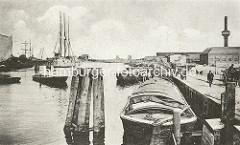 Historische Ansicht aus dem Harburger Hafen - Binnenschiffe liegen am Kai, ein Segelschiff liegt in der Mitte des Hafenbeckens. (ca. 1910)