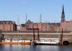 Arbeitsschiffe im Grasbookhafen am Dalmannkai - im Hintergrund Speichergebäude in der Hamburger Speicherstadt - in der Mitte das ehem. Kesselhaus.