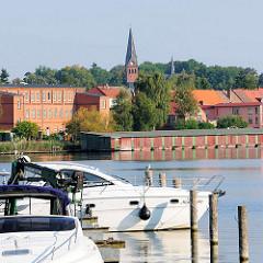 Sportboote am Ufer des Malchower Sees - Bootshäuser am Seeufer; Kirchturm der neogotischen Stadtkirche von Malchow.