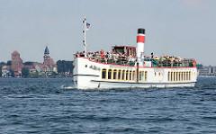 Fahrgastschiff, Dampfschiff EUROPA der Weissen Flotte Müritz auf der Binnenmüritz; Passagiere / Touristen sitzen auf dem Oberdeck in der Sonne - im Hintergrund die Kirchtürme der Stadt Waren (Müritz).